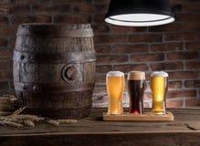 Os vidros da cerveja e da cerveja inglesa barrel na tabela de madeira Cervejeiro do ofício imagem de stock