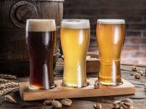 Os vidros da cerveja e da cerveja inglesa barrel na tabela de madeira Cervejeiro do ofício Foto de Stock Royalty Free