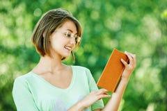 Os vidros da mulher nova leram o livro Fotografia de Stock