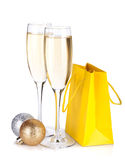 Os vidros de Champagne, os baubles do Natal e o presente ensacam Fotografia de Stock