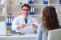 Os vidros de prescrição do ótico do doutor a um paciente fotos de stock royalty free