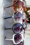 Os vidros de sol dos óculos de sol empilhados enfileiram no indicador da loja Fotos de Stock Royalty Free