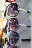 Os vidros de sol dos óculos de sol empilhados enfileiram no indicador da loja Foto de Stock Royalty Free