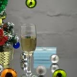 Os vidros de vinho com champanhe efervescente, presente, Natal brincam no fundo bege imagens de stock royalty free