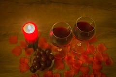 Os vidros de vinho tinto, uvas, vela de queimadura, e aumentaram as folhas na tabela imagens de stock royalty free