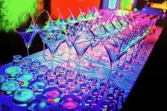 Os vidros de vinho vazios coloridos sobrepõem no contador da barra no partido do clube noturno Imagens de Stock