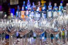 Os vidros de vinho vazios com cor borram o fundo na barra Imagens de Stock Royalty Free