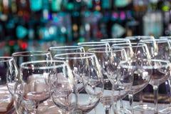 Os vidros de vinho vazios com cor borram o fundo na barra Imagem de Stock