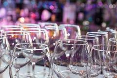 Os vidros de vinho vazios com cor borram o fundo na barra Foto de Stock
