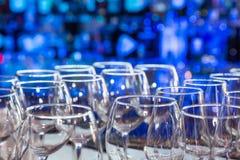 Os vidros de vinho vazios com cor borram o fundo na barra Fotos de Stock Royalty Free