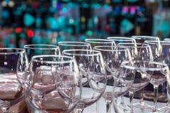 Os vidros de vinho vazios com cor borram o fundo na barra Fotos de Stock
