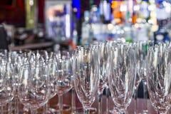Os vidros de vinho vazios com cor borram o fundo na barra Foto de Stock Royalty Free