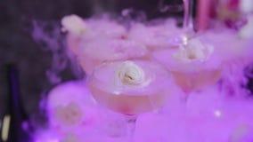 Os vidros do close-up são sobre se sob a forma de uma pirâmide e fluíram champanhe dos vidros são fumo branco filme