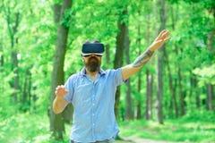 Os vidros do desgaste de homem VR do Gamer no Gamer da floresta do verão jogam o jogo da realidade virtual com dispositivo móvel  Imagem de Stock Royalty Free