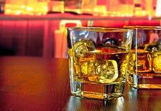 Os vidros do uísque com gelo na barra apresentam perto da garrafa de uísque na atmosfera morna Fotografia de Stock