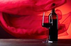 Os vidros e a garrafa do rede wine em um fundo vermelho F completo vermelho Foto de Stock Royalty Free