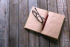 Os vidros encerram e livro na tabela de madeira para o engodo do negócio ou da educação Imagem de Stock