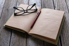 Os vidros encerram e livro na tabela de madeira para o engodo do negócio ou da educação Imagens de Stock