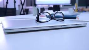 Os vidros encontram-se no portátil na mesa de escritório, close-up vídeos de arquivo
