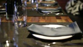 Os vidros, forquilhas, facas, placas em uma tabela no restaurante serviram para o jantar vídeos de arquivo