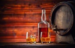 Os vidros, a garrafa e o barril do uísque com cubos de gelo serviram na madeira Imagem de Stock