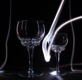 Os vidros mostram em silhueta o vidro bebendo em um illumin preto do fundo Foto de Stock