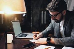 Os vidros, o smartwatch e o escritório farpados novos vestir de homem vestem usando o portátil moderno no escritório do sótão da  Imagens de Stock