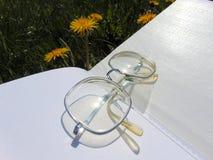 Os vidros que colocam no livro aberto com jardim florescem no fundo fotos de stock