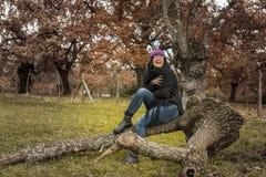 Os vidros vestindo da mulher e o riso roxo do chapéu de lãs sentam-se em uma árvore Fotografia de Stock Royalty Free