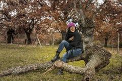 Os vidros vestindo da mulher feliz, as calças de brim e as botas pretas sentam-se em uma árvore Imagens de Stock