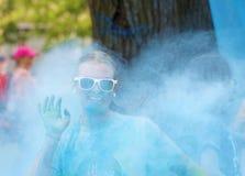 Os vidros vestindo de sorriso da jovem mulher esguincharam com o dus azul da cor Foto de Stock Royalty Free