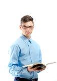 Os vidros vestindo do adolescente leram o formulário que um livro se isolou no branco Imagem de Stock Royalty Free
