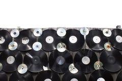 Os vinis e o CD são parafusados a uma cerca no fundo branco, isolado fotos de stock