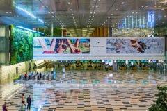 Os visitantes andam em torno da área de Hall Immigration da chegada no ar de Changi fotografia de stock