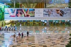 Os visitantes andam em torno da área de Hall Immigration da chegada no ar de Changi foto de stock royalty free