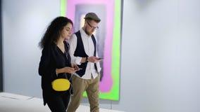 Os visitantes da exposição da pintura moderna são comentários de escuta pelo guia audio filme