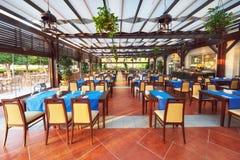 Os visitantes de espera servidos vazios da tabela do restaurante são ficados situados na praia Amara Dolce Vita Luxury Hotel recu Imagens de Stock Royalty Free