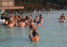 Os visitantes geotérmicas dos termas com máscaras da lama do silicone relaxam e refrescam na lagoa azul famosa Imagem de Stock