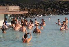Os visitantes geotérmicas dos termas com máscaras da lama do silicone relaxam e refrescam na lagoa azul famosa Fotos de Stock