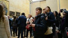 Os visitantes tomam fotos perto de Leonardo DaVincis Mona Lisa, museu do Louvre, vídeos de arquivo