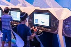 Os visitantes usam simuladores visuais sob a supervisão de um instrutor do exército no ` da exposição do exército nosso ` do IDF foto de stock