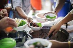 Os voluntários dão o alimento aos pobres: doar o alimento está ajudando amigos humanos na sociedade: Povos de ajuda com fome com  foto de stock