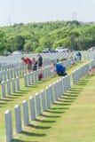 Os voluntários e os membros da família colocam bandeiras nas cabeças caídas dos heróis imagens de stock royalty free