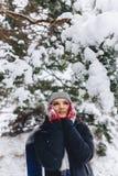 Os warmes da menina seus mordentes nas luvas no inverno frio no p foto de stock
