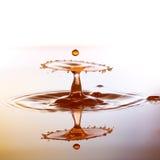 Os waterdrops pequenos de uma cor caem na superfície da água e Fotos de Stock Royalty Free