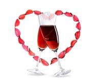 Os Wineglasses com vinho vermelho dentro de um coração dão forma imagens de stock