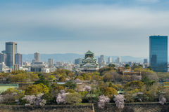 Osaka castle with cherry blossom and center business district in. Background at Osaka, Japan. Japan spring beautiful scene Stock Images