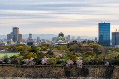 Osaka castle with cherry blossom and Osaka center business dictr. Ick in background atOsaka, Japan. Japan spring beautiful scene Royalty Free Stock Photo