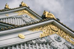 Osaka Castle facade details with golden ornaments in Japan. Plant inspired golden ornaments at Osaka Castle Pagoda with white walls and specific green roof tiles royalty free stock image