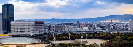 Osaka cityscape with overcast sky. Osaka city skyline with a baseball field and park  in the foreground and mountains in the background Stock Photography